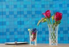 Foto conservada em estoque: Grupo de rosas cor-de-rosa no vaso com presente cor-de-rosa e blan Imagem de Stock