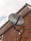 Foto conservada em estoque - um satélite preto do prato do céu fecha-se acima na parede de tijolo Fotos de Stock