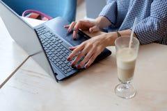 Foto cosechada de la mujer joven con la taza de café que mecanografía por el ordenador portátil Imagenes de archivo
