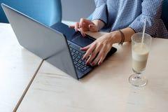 Foto cosechada de la mujer joven con la taza de café que mecanografía por el ordenador portátil Fotos de archivo libres de regalías