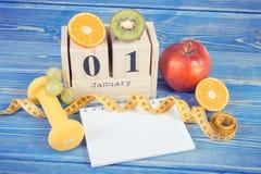 Foto d'annata, data del 1° gennaio, frutti, teste di legno e misura di nastro, nuovi anni di risoluzioni Fotografie Stock