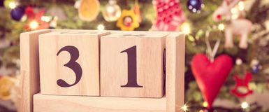 Foto d'annata, data 31 dicembre sul calendario ed albero di Natale con la decorazione, nuovi anni di concetto di vigilia Immagini Stock