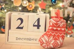 Foto d'annata, data 24 dicembre sul calendario, regalo in calzino ed albero di Natale con la decorazione, tempo di notte di Natal Fotografie Stock