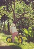 Foto d'annata di piccolo bambino che guida una bicicletta sull'erba verde Immagine Stock