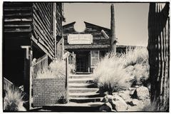 Foto d'annata di seppia in bianco e nero di vecchie costruzioni di legno occidentali nella città fantasma della miniera d'oro di  immagine stock libera da diritti