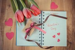 Foto d'annata, giorno di biglietti di S. Valentino scritto in taccuino, tulipani freschi, regalo avvolto e cuori, decorazione per Immagine Stock