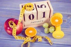 Foto d'annata, il 1° gennaio sul calendario del cubo, sui frutti, sulle teste di legno e sulla misura di nastro, nuovi anni di ri Fotografia Stock
