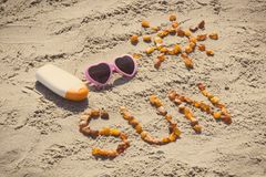 Foto d'annata, parola e forma del sole, occhiali da sole con la lozione del sole sulla sabbia alla spiaggia, concetto di ora lega Fotografia Stock