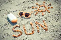 Foto d'annata, parola e forma del sole, occhiali da sole con la lozione del sole sulla sabbia alla spiaggia, ora legale Fotografia Stock