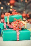 Foto d'annata, regali avvolti variopinti ed albero di Natale con le luci nel fondo fotografia stock