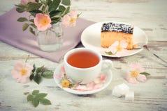 Foto d'annata, tazza di tè con torta di formaggio e fiore rosa selvaggio su vecchio fondo di legno Immagine Stock