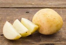Foto da batata e das fatias na tabela de madeira Imagens de Stock Royalty Free