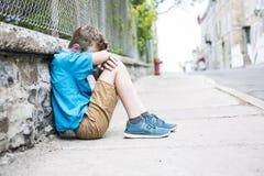 A foto da criança triste e forçada senta-se pela parede exterior fotografia de stock royalty free