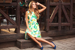 Foto da forma da rua da mulher bonita nova que senta-se no sta Fotografia de Stock Royalty Free