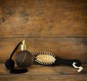 Foto da garrafa de perfume do vintage ao lado da escova de cabelo de madeira velha na tabela de madeira imagem filtrada retro Fotos de Stock Royalty Free