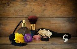 Foto da garrafa de perfume do vintage ao lado da escova de cabelo de madeira velha na tabela de madeira imagem filtrada retro Foto de Stock