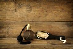 Foto da garrafa de perfume do vintage ao lado da escova de cabelo de madeira velha na tabela de madeira imagem filtrada retro Fotos de Stock