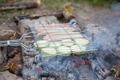 Foto da grade para o assado com vegetais e salsichas no fogo na floresta imagem de stock royalty free