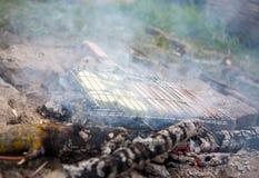 Foto da grade para o assado com vegetais e salsichas no fogo na floresta fotos de stock royalty free