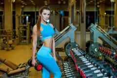 Foto da jovem mulher 'sexy' que descansa no gym e que inclina-se na fileira dos pesos imagem de stock