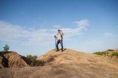 Foto da lontano dell'uomo turistico con i bastoni da passeggio sulla collina della montagna Fotografie Stock