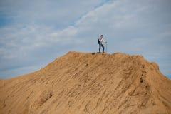 Foto da lontano dell'uomo turistico con lo zaino ed i bastoni per la camminata sulla collina Fotografia Stock Libera da Diritti