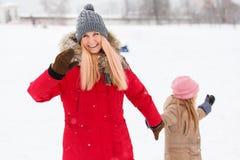 A foto da mãe feliz e a filha na caminhada no inverno estacionam fotos de stock royalty free