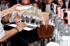 Foto da mão do empregado de bar que guarda a garrafa e que derrama a água fora dela no evento do partido Imagem de Stock Royalty Free