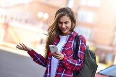 Foto da menina bonito que anda na rua e que usa um smatphone fotografia de stock