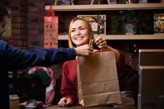 Foto da menina de sorriso do vendedor que dá o saco de papel ao comprador masculino imagens de stock