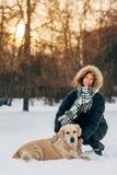 Foto da menina de sorriso na caminhada com o cão no fundo das árvores imagem de stock