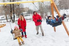 Foto da menina feliz e do menino que balançam no inverno no parque com pais fotografia de stock