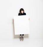 Foto da menina que salta na galeria moderna e que olha a lona branca vazia Horizontal, modelo imagens de stock