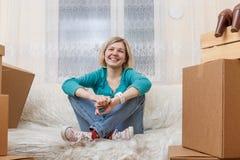 Foto da menina que senta-se no sofá entre caixas de cartão fotografia de stock royalty free