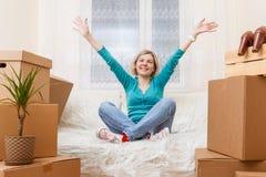 Foto da menina que senta-se no sofá entre caixas de cartão foto de stock royalty free