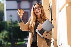 Foto da mulher adorável que bebe o café afastado ao andar através da rua da cidade fotografia de stock royalty free
