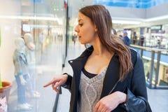 Foto da mulher alegre nova com a bolsa no fundo de sh Fotografia de Stock Royalty Free
