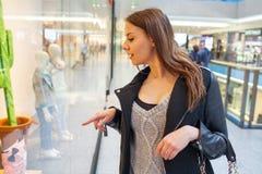 Foto da mulher alegre nova com a bolsa no fundo de sh Fotos de Stock Royalty Free