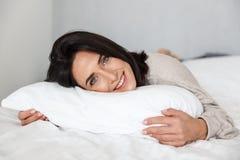 Foto da mulher alegre 30s que sorri, ao encontrar-se na cama com linho branco em casa imagens de stock