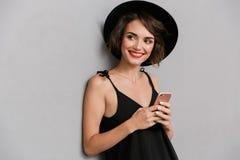 Foto da mulher atrativa 20s que veste o smilin preto do vestido e do chapéu foto de stock