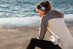 Foto da mulher bonita do esporte que escuta a música, ao descansar o af imagem de stock royalty free