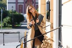 Foto da mulher bonita que bebe o café afastado ao andar através da rua da cidade foto de stock