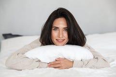 Foto da mulher de meia idade 30s que sorri, ao encontrar-se na cama com linho branco em casa foto de stock