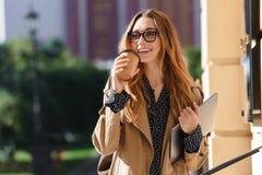 Foto da mulher de negócios que bebe o café afastado ao andar através da rua da cidade fotografia de stock royalty free
