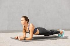 A foto da mulher faz o exercício estático da prancha, tem a expressão alegre, exulta a realização do bom resultado, afrouxando o  fotos de stock