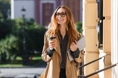 Foto da mulher moderna 20s que bebe o café afastado ao andar através da rua da cidade fotos de stock royalty free
