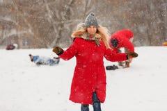 Foto da mulher no revestimento vermelho durante a queda de neve fotos de stock royalty free