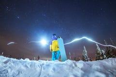 Foto da noite do snowboarder da senhora contra montanhas da noite Foto de Stock Royalty Free