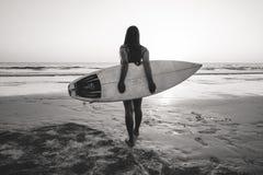 Foto da nostalgia e da relembrança da mulher do surfista no biquini para ir a surfar fotografia de stock royalty free
