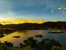 Foto da paisagem da luz solar que dispersa através das nuvens acima do campo aberto perto de um lago fotos de stock royalty free